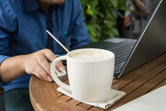 Man with a cup of coffee working on his laptop. Man working Stock Image