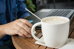 Man with a cup of coffee working on his laptop. Man working Stock Photos