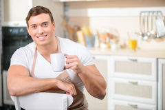 Man with a cup of drink in the kitchen Royalty Free Stock Images