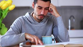 Man with cup of drink reading a book at kitchen stock footage