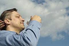 Man with cup drinks on nature. Happy man with cup drinks on nature sky background Stock Image