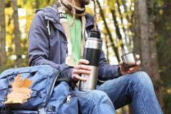 Man with cup of hot drink - tea or coffee and thermos sits in autumn forest with backpack, maple leaf stock photo