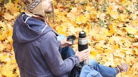 Man with cup of hot drink - tea or coffee and thermos sits in autumn forest with backpack, rear view stock photography
