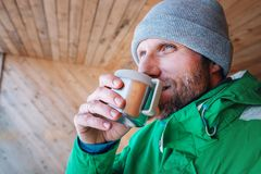 Man with cup of hot drink warms on open winter air Stock Image