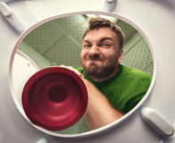 Man with cup plunger. Man cleaning the toilet with cup plunger stock photos