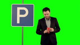 Man with cup of tea near parking sign on a Green. Screen, Chroma Key. Professional shot on BMCC RAW with high dynamic range. You can use it e.g in your stock footage