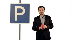 Man with cup of tea near parking sign on white background isolated. Professional shot on BMCC RAW with high dynamic range. You can use it e.g in your royalty free stock photo