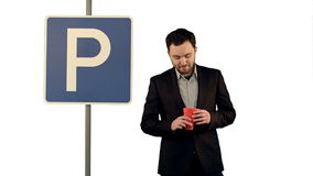 Man with cup of tea near parking sign on white. Background isolated. Professional shot on BMCC RAW with high dynamic range. You can use it e.g in your stock video footage