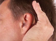 Man cupping his hand behind his ear Stock Image