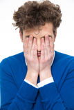 Man with curly hair covers his face Royalty Free Stock Photo