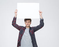 Man with curly hair holding blank billboard Stock Image