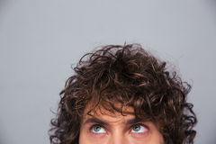 Man with curly hair looking up at copyspace Stock Photography