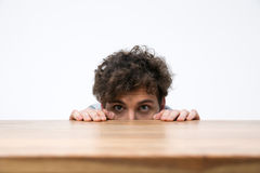 Man with curly hair peeking from behind the desk Stock Photos