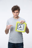 Man with curly hair pointing on the clock Royalty Free Stock Photography