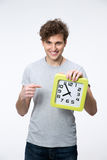 Man with curly hair pointing on the clock Stock Photo