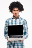 Man with curly hair showing blank laptop computer screen. Portrait of a smiling afro american man with curly hair showing blank laptop computer screen isolated Royalty Free Stock Photo