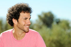 Man with curly hairstyle smiling, outdoors Royalty Free Stock Image