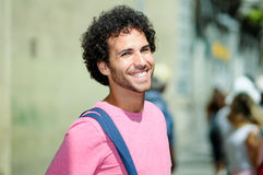 Man curly hairstyle smiling in urban background Stock Photo
