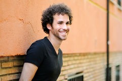 Man curly hairstyle smiling in urban background Stock Image