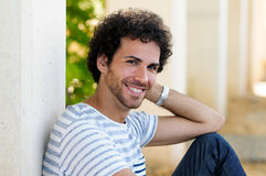 Man with curly hairstyle smiling in urban background Stock Photo