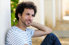 Man with curly hairstyle smiling in urban background Stock Photography