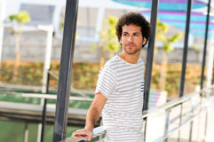 Man with curly hairstyle in urban background Stock Photo