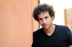 Man with curly hairstyle in urban background Stock Photos