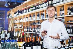 Man customer holding glass of wine. Young man customer holding glass of wine before buy it in a wine house Royalty Free Stock Photo