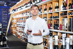 Man customer holding glass of wine. Young man customer holding glass of wine before buy it at wine house Stock Images