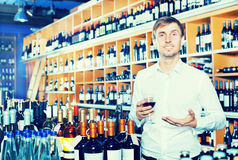 Man customer holding glass of wine. Young man customer holding glass of wine before buy it in a wine house Stock Photography