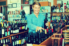 Man customer holding wine bottle in hands Stock Images