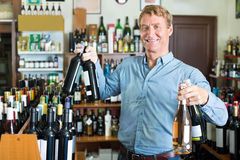 Man customer holding wine bottle in hands Stock Photos