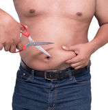 Man Cut belly fat and cellulite by scissors weight loss concept Royalty Free Stock Image