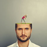 Man with cut head. Portrait of displeased men with cut head. small pretty women doing fitness exercises on the green meadow in mans head. photo over grey Royalty Free Stock Photos