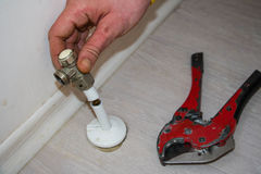 Man cut plastic pipe radiator with scissors. Worker removed radiator valve with scissors Stock Photos