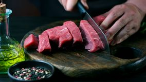 Man cut raw beef on steak pieces stock video footage