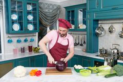 A Man cut red cabbage with white knife. Handsome chef cut red cabbage. Red cabbage cut by knife. Men love cooking fresh salad stock image