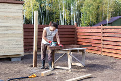 Man cut wooden beam with circular saw Royalty Free Stock Photos