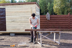 Man cut wooden beam with circular saw Stock Photo