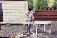 Man cut wooden beam with circular saw Royalty Free Stock Photo