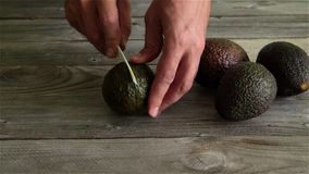 Man cuts avocado on an old wooden table with a knife. Full hd video stock footage