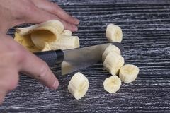 A man cuts a banana knife into slices on an old black wooden table stock image