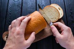 Man cuts bread Royalty Free Stock Photos