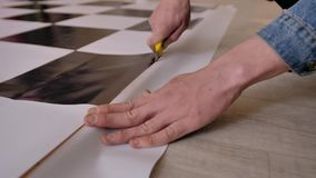 A man cuts a canvas with a stationery knife holding it with one hand. Close-up hands. The canvas is on the floor. stock video footage