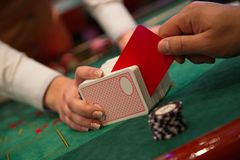 Man cuts cards with a red card.  Royalty Free Stock Images
