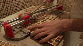 Man cuts ceramic tile for bathroom stock video