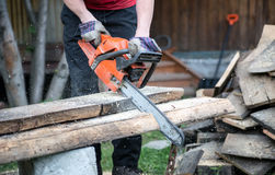 Man cuts chainsaw board outdoors Stock Image