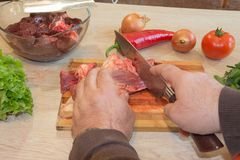 Man cuts of fresh piece of meat on a wooden cutting board in the home kitchen. Preparing meal, meat and vegetables Royalty Free Stock Photos