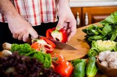 Man cuts fresh spring vegetables Royalty Free Stock Photo
