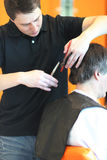 A man cuts hair in a barbershop Stock Images